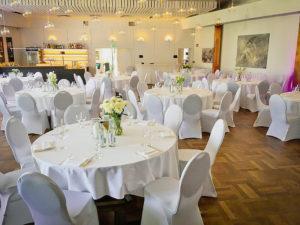 C.ulturgut-Saal mit festlich eingedeckten Tischen